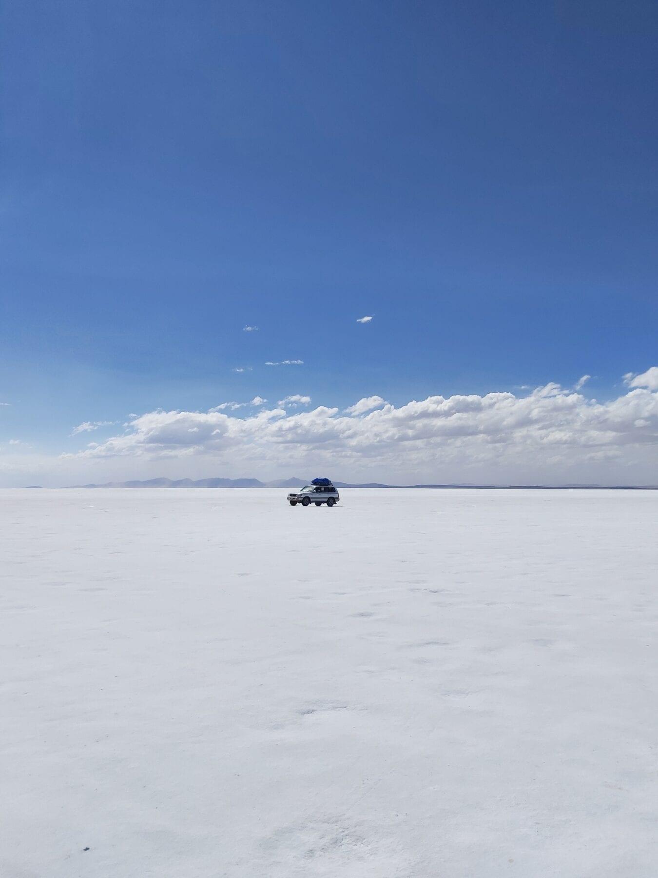 Auto op de zoutvlakte in Bolivia